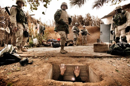 Yuri Kozyrev, A journalist climbs out of the hole where toppled dictator Saddam Hussein was captured in Ad Dawr. Iraq's defeated leader raised his arms out of his 'rat hole' and said he was Saddam Hussein and that he wanted to negotiate, Iraq, December 15, 2003.