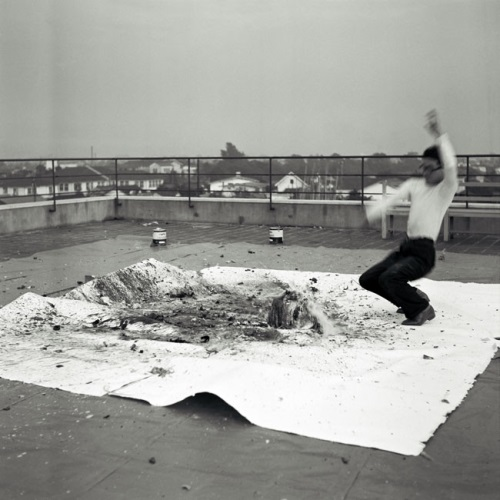 Shimamoto Shōzō making a painting by throwing glass bottles of paint against a canvas, 1956.