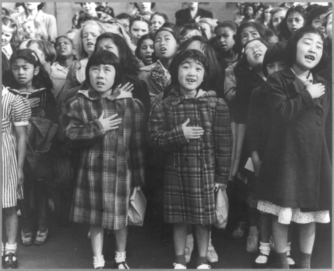 "Dorothea Lange, ""San Francisco, Calif., April 1942 - Children of the Weill public school, from the so-called international settlement, shown in a flag pledge ceremony. Some of them are evacuees of Japanese ancestry who will be housed in War relocation authority centers for the duration,"" 1942."